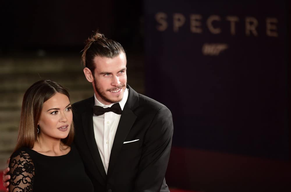 Welsh footballer Gareth Bale (R) and his wife Emma Rhys Jones pose on arrival for the world premiere of the new James Bond film 'Spectre' at the Royal Albert Hall in London on October 26, 2015. The film is directed by Sam Mendes and sees Daniel Craig play suave MI6 spy 007 for a fourth time. AFP PHOTO / LEON NEAL